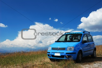 Bright pale blue modern car with beautiful nature background