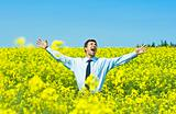 businessman happy in a field of yellow flowers