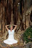 Woman meditating in front of Bodhi Tree roots