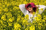 Smiling girl in the rapeseed yellow field