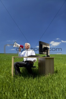 Business Concept Man Using Megaphone In A Green Field