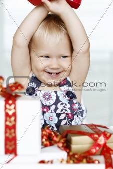 Little girl gleefully opening Christmas gifts.