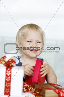 Little girl gleefully opening Christmas gifts.
