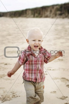 A happy little boy at the beach.