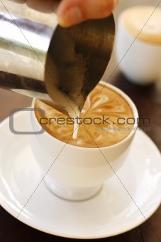 A barista creating latte coffee art.