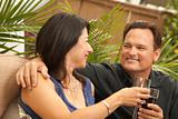 Attractive Hispanic and Caucasian Couple Drinking Wine Outside.