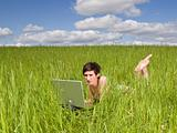 Woman with a computer in the grass
