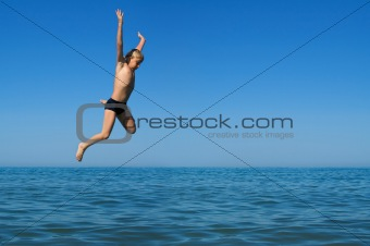 Boy jumping into the sea