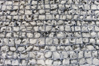 Old road made of stone bricks. Abstract texture background.