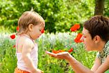 Mother showing poppy flower 