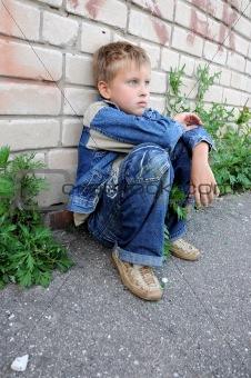 young man sitting against graffiti