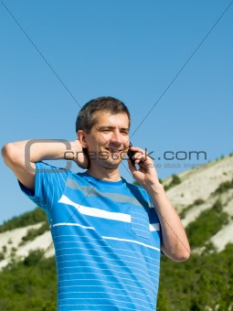 a man is talking over the phone at the mountains