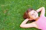 Sweet little girl lying on a grassy meadow