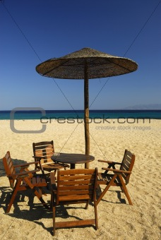 Chairs, table and grass-umbrella on the  beach.