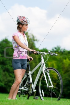 Girl standing with a bicycle