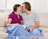 Couple kissing on couch