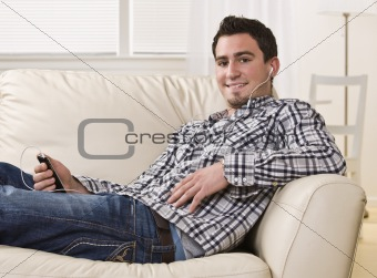 Attractive brunette male sitting on couch.