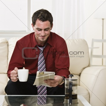 Attractive male drinking coffee and reading a newspaper