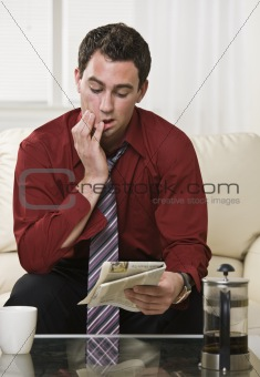 Attractive male reading Newspaper