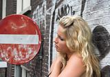 Attractive blonde standing next to a red road sign