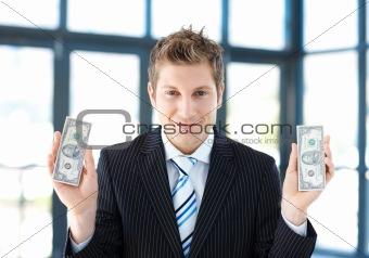 Attractive businessman holding dollars