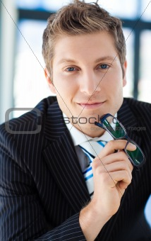 Businessman looking to the camera holding glasses