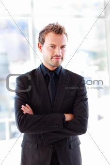 Attractive confident businessman with folded arms