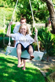 Dad and kid having fun swinging together