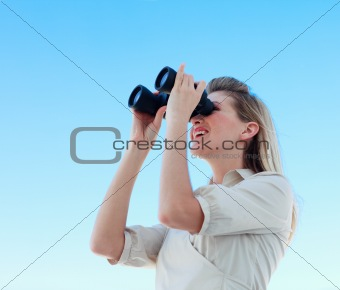 Blonde businesswoman looking through binoculars