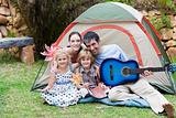 Family camping and playing a guitar