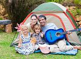 Family playing a guitar in a tent
