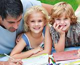 Smiling children drawing with their father