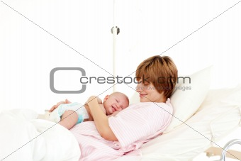 Happy patient with newborn baby in bed