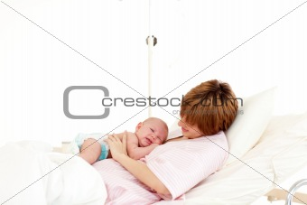 Patient speaking to her newborn baby in bed
