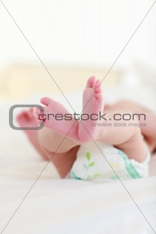 Baby lying on bed