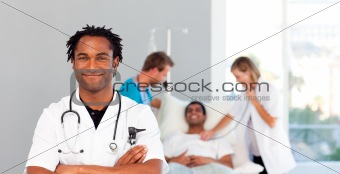 Portrait of an African doctor with a patient in the background