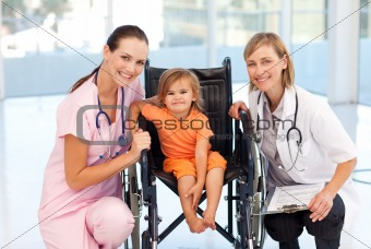 Baby in a wheelchair with nurse and doctor