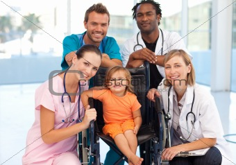 Group of doctors with a little girl in a wheelchair
