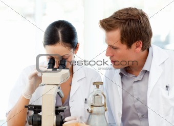 Scientists looking through a microscope