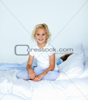 Smiling blonde girl sitting on a bed