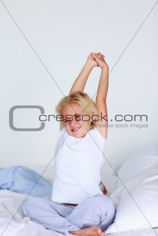 Blonde girl stretching in bed