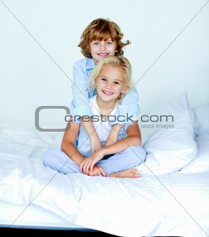 Portrait of young siblings in bed