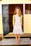 Portrait of a pretty young girl standing outside her playhouse.