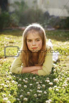 A pretty young girl lying on the grass amongst flowers.