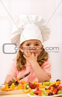 Little girl chief making fresh fruit salad