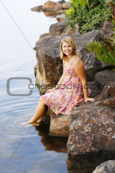 Beautiful young blonde woman at the water's edge.