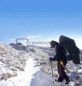 backpacker with heavy pack walk on the snow