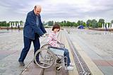 Man pushing woman in wheelchair