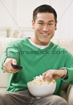 Attractive Asian Man with Popcorn and Remote Control