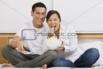 Attractive Asian Couple Eating Popcorn in Bed